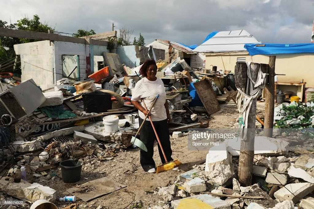 Flo Webber stands amongst the debris of her home on the nearly destroyed island of Barbuda on December 8, 2017 in Cordington, Barbuda. Barbuda, which covers only 62 square miles, was nearly leveled when Hurricane Irma made landfall with 185mph winds on the night of September six. Only two days later, fearing Barbuda would be hit again by Hurricane Jose, the prime minister ordered an evacuation of all 1,800 residents of the island. Most are now still in shelters scattered around Barbuda's much larger sister island Antigua.