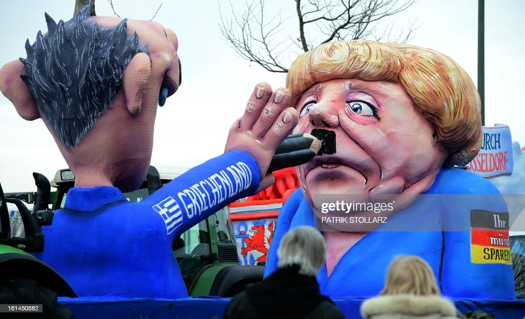 A float featuring a Greek drawing a mustache at German chancellor Angela Merkel is seen in the streets of Duesseldorf during the traditional Rose Monday parade on February 11, 2013. Carnival goers mainly in the Rhine region traditionally celebrate the highlight procession on Rosenmontag (Rose Monday). The season ends with Ash Wednesday on February 13, 2013.