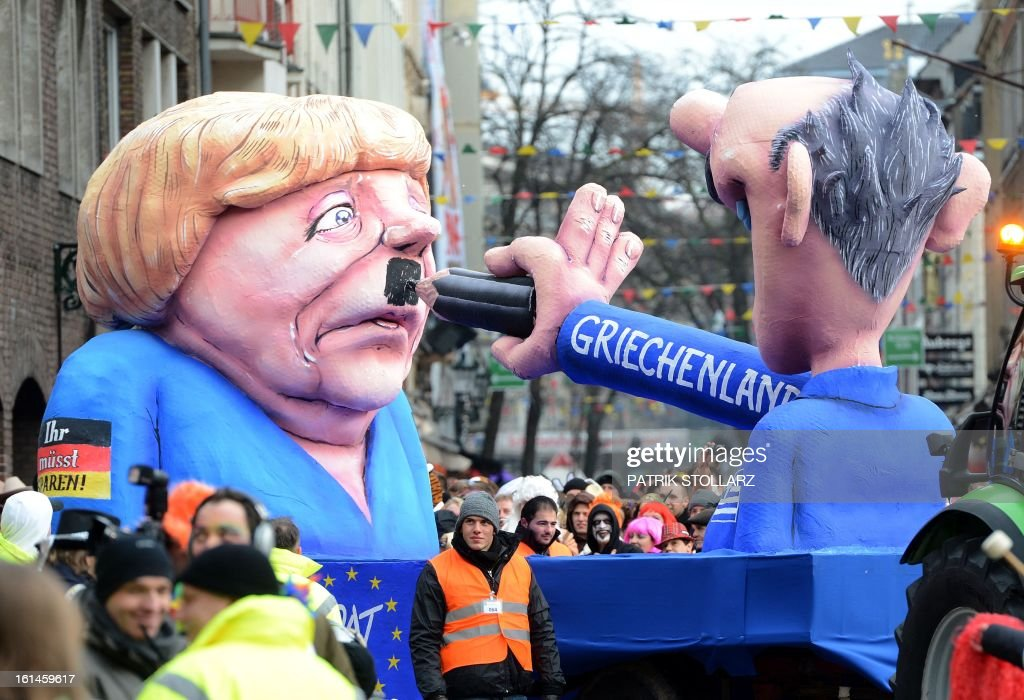A float featuring a Greek drawing a mustache to German chancellor Angela Merkel makes its way through the streets of Duesseldorf during the traditional Rose Monday parade on February 11, 2013. Carnival goers mainly in the Rhine region traditionally celebrate the highlight procession on Rosenmontag (Rose Monday). The season ends with Ash Wednesday on February 13, 2013.