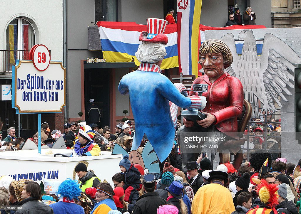 A float featuring likenesses of German Chancellor Angela Merkel (R) and the NSA with text reading 'the spy who came out of the mobile phone'makes its way through the streets of Mainz as people celebrate the carnival during the traditional Rose Monday parade in Mainz, western Germany, on March 3, 2014. Carnival goers mainly in the Rhine region traditionally celebrate the highlight procession on Rosenmontag (Rose Monday).