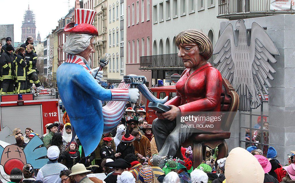 A float featuring likenesses of German Chancellor Angela Merkel (R) and the NSA with text reading 'the spy who came out of the mobile phone'makes its way through the streets of Mainz as people celebrate the carnival during the traditional Rose Monday parade in Mainz, western Germany, on March 3, 2014. Carnival goers mainly in the Rhine region traditionally celebrate the highlight procession on Rosenmontag (Rose Monday). AFP PHOTO / DANIEL ROLAND
