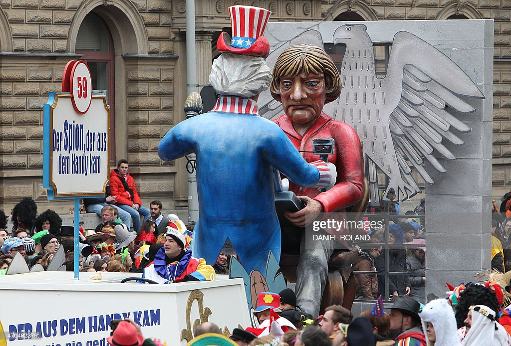 A float featuring likenesses of German Chancellor Angela Merkel and the NSA with text reading 'the spy who came out of the mobile phone'makes its way through the streets of Mainz as people celebrate the carnival during the traditional Rose Monday parade in Mainz, western Germany, on March 3, 2014. Carnival goers mainly in the Rhine region traditionally celebrate the highlight procession on Rosenmontag (Rose Monday).