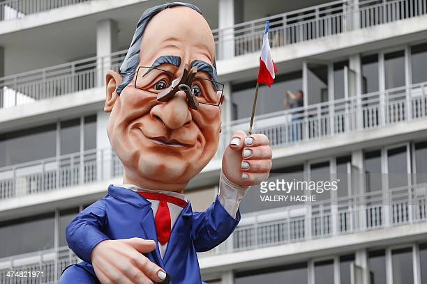A float named 'Cheeses of Hollande' and featuring French President Francois Hollande waving a French flag with a clothespin on his nose parades...
