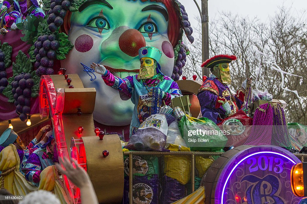 Float riders toss beads, cups and doubloons to fans and revelers in the 2013 Krewe of Bacchus Mardi Gras Parade on February 10, 2013 in New Orleans, Louisiana.