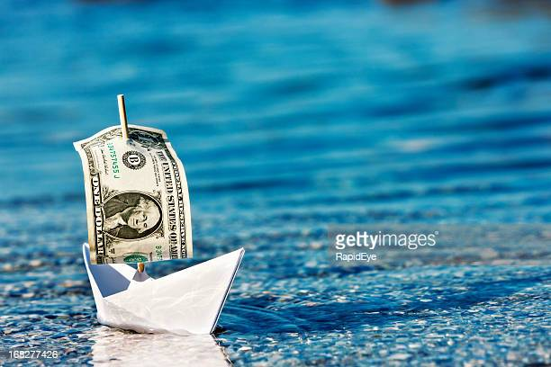 Floating a company? Paper boat with dollar bill sail