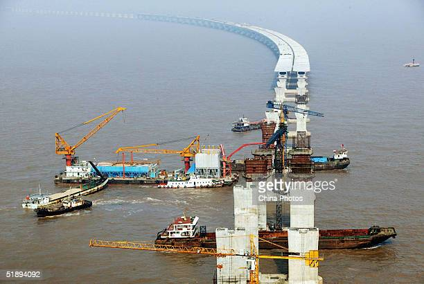 A floating crane lifts a segment of box girder to place it on the piers at the construction site of the East Sea Bridge on December 25 2004 in...
