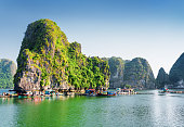 Floating fishing village in the Halong Bay (Descending Dragon Bay) at the Gulf of Tonkin of the South China Sea, Vietnam. The Ha Long Bay is a popular tourist destination of Asia.