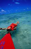 Floating in ocean near kayak.