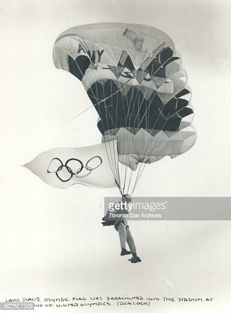 Floating in the flag The Olympic flag its five rings representing the five continents is parachuted through cloudy skies into Lake Placid stadium to...