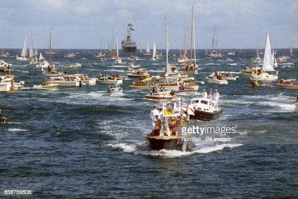A floating 'traffic jam' of small craft as the Royal Barge brings Queen Elizabeth II and the Duke of Edinburgh ashore from the Royal Yacht Britannia...