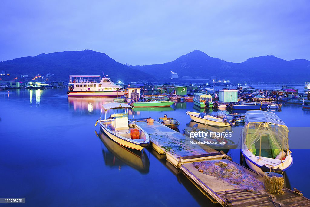 Floating village and moored boats at dusk