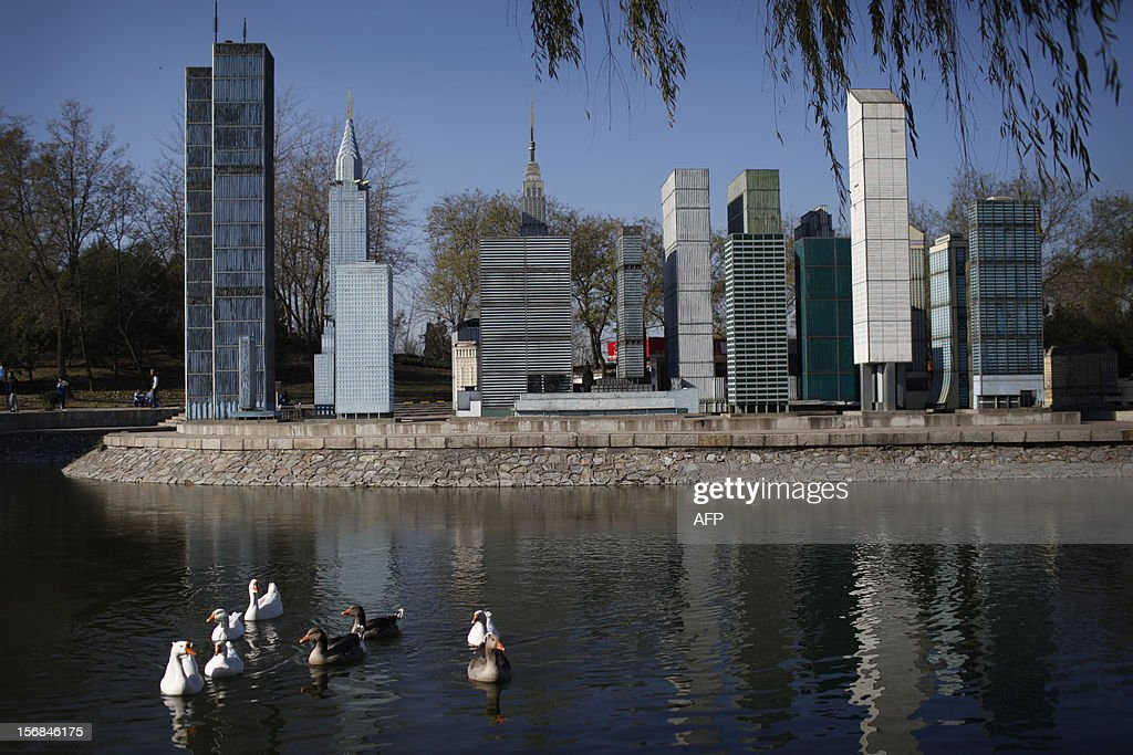 A flock of ducks swam pass the mini replica of Manhattan buildings in Beijing World Park, in the southwestern suburb of Beijing on November 23, 2012. Beijing World Park, with a collection of mini replicas of famous architectures from all over the wolrd, attempts to give visitors a chance to see the world without having to leave Beijing. CHINA OUT AFP PHOTO