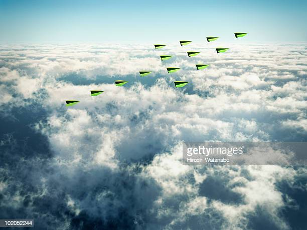 Flock of paper airplanes above clouds in arrow for