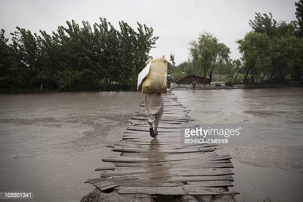 A flododaffected Pakistani man carries his belongings as he walks on a wooden bridge towards the village of Shah Alam on the outskirts of Peshawar on...