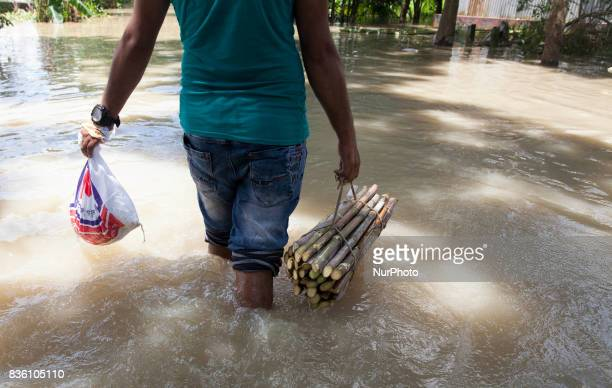A flood affected men cross flood water with a foods near a river Padma at Dohar Nawabganj Bangladesh 19 August 2017 According to authorities floods...
