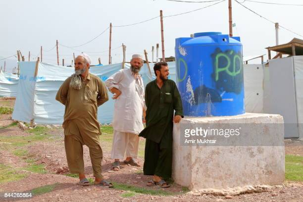 Flood Affected People Standing Near Water Tank