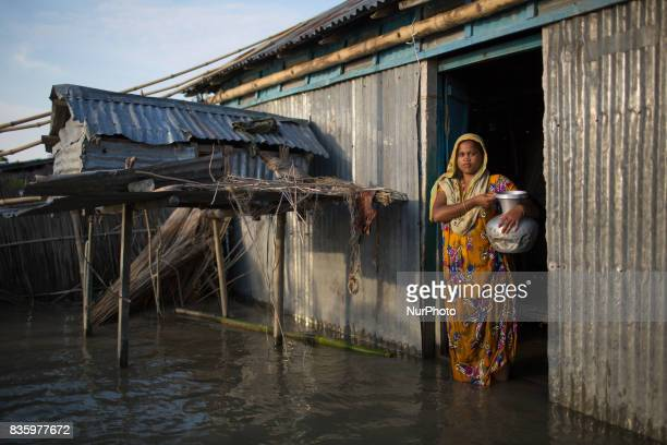 A flood affected village woman poses for a photograph in front of her house which is affected by flood Sariakndi outskirt of Bogra Bangladesh August...