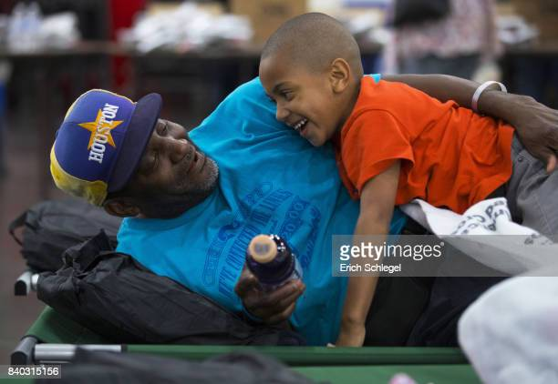 Flood evacuee from Houston's 5th Ward Korbey Haley shares a light moment with his son Jordan Haley 6 at the George Brown Convention Center which has...