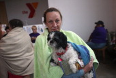Flood evacuee Stacy Ford holds her dog Sugar while at a shelter set up in a YMCA on August 29 2012 in Plaquemines Parish Louisiana the most heavily...