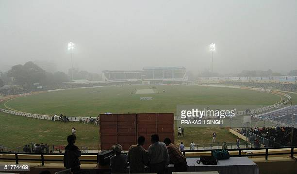 Flood lights are on on a foggy morning at the Green Park stadium in Kanpur 22 November 2004 as bad weather resulted in the late start of the third...