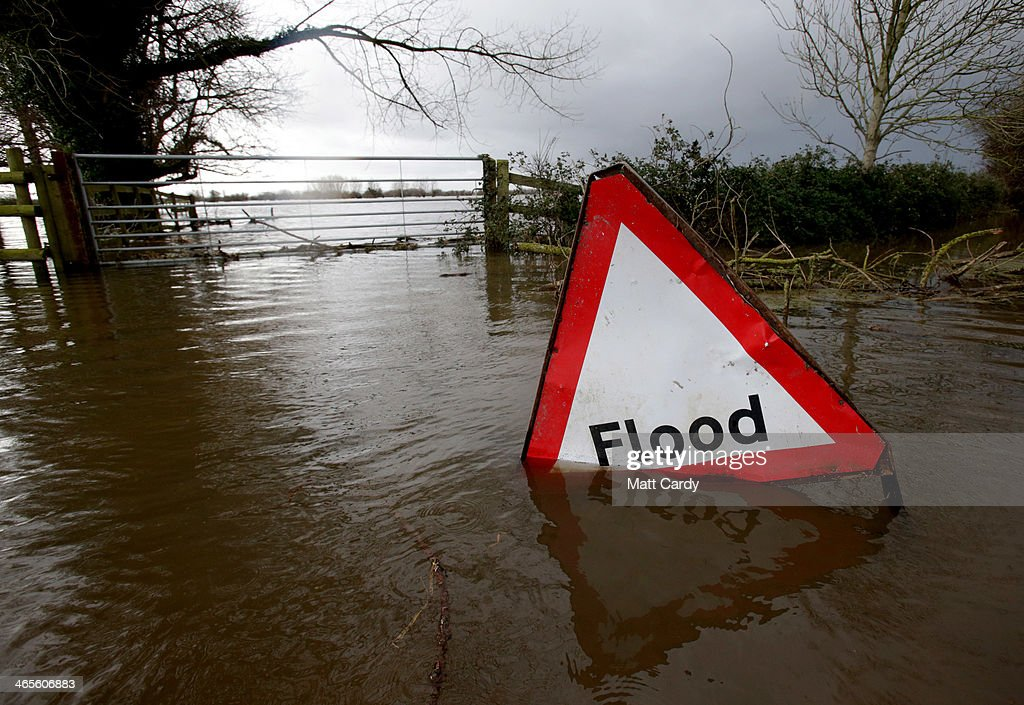 A flood sign is seen in flood waters surrounding farm buildings on January 28 2014 in Somerset England As Lord Smith the chairman of the Environment...