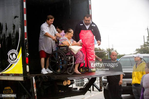 A flood victim in a wheel chair is helped off a delivery truck after being rescued from his home to be escorted to shelters from Walmart parking lot...