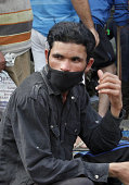A flood victim wears a protective mask as he waits to receive medical help at camp Rajbag area on September 12 2014 in Srinagar India Total of 130000...