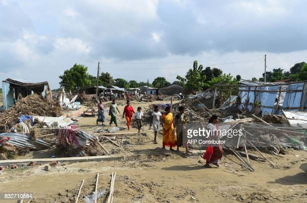 Flood victims arrive to collect relief material as they walk past damaged houses in Itahari Sunsari district some 250 kms from Nepal's capital...