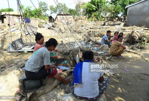 Flood victims collect their belongings from damaged house hit by flood in Itahari Sunsari district some 250 kms from Nepal's capital Kathmandu on...