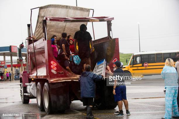 Flood victims gather their belongings after being rescued from their home to be escorted to shelters from Walmart parking lot to Channelview High...