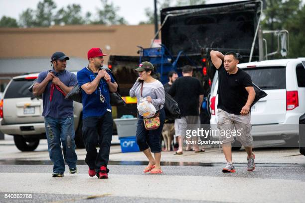 Flood victims gather their belongings to be escorted to shelters from Walmart parking lot to Channelview High School for safety during Hurricane...