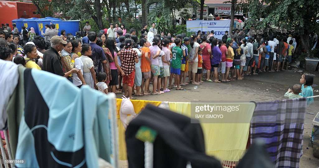 Flood victims line up for relief at a shelter in Jakarta on January 23, 2013. A spokesman for Indonesian National Disaster Mitigation Agency (BNPB) said more than 30,000 people were still living as refugees on January 22, while 20 people were killed during the widespread flooding that hit Jakarta. AFP PHOTO / Bay ISMOYO