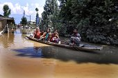 Flood victims make their way through an intersection of a submerged road as they make their way to safer places on September 11 2014 in Srinagar...