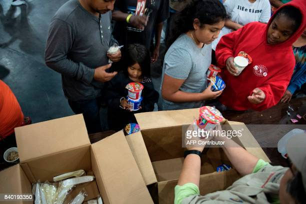 Flood victims receive food at a shelter in the George R Brown Convention Center during the aftermath of Hurricane Harvey on August 28 2017 in Houston...