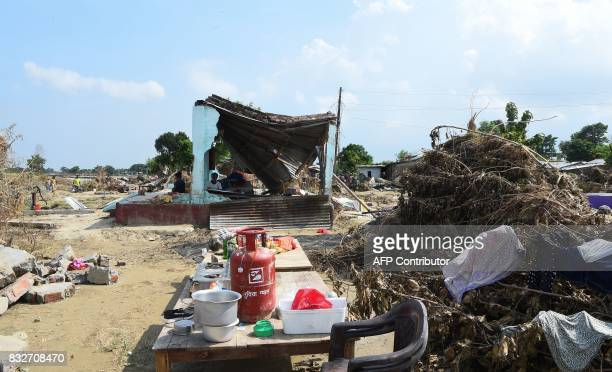 Flood victims rest in their damaged house in Itahari Sunsari district some 250 kms from Nepal's capital Kathmandu on August 16 2017 At least 221...