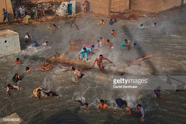 Flood victims scramble for food rations as they battle the downwash from a Pakistan Army helicopter during relief operations on September 13 2010 in...