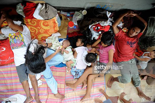 Flood victims take shelter in a church used as an evacuation centre in Quezon City suburban Manila on August 9 2012 Philippine authorities appealed...