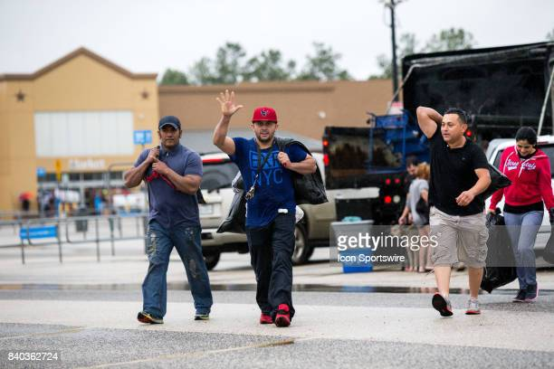 Flood victims waves after gathering their belongings to be escorted to shelters from Walmart parking lot to Channelview High School for safety during...