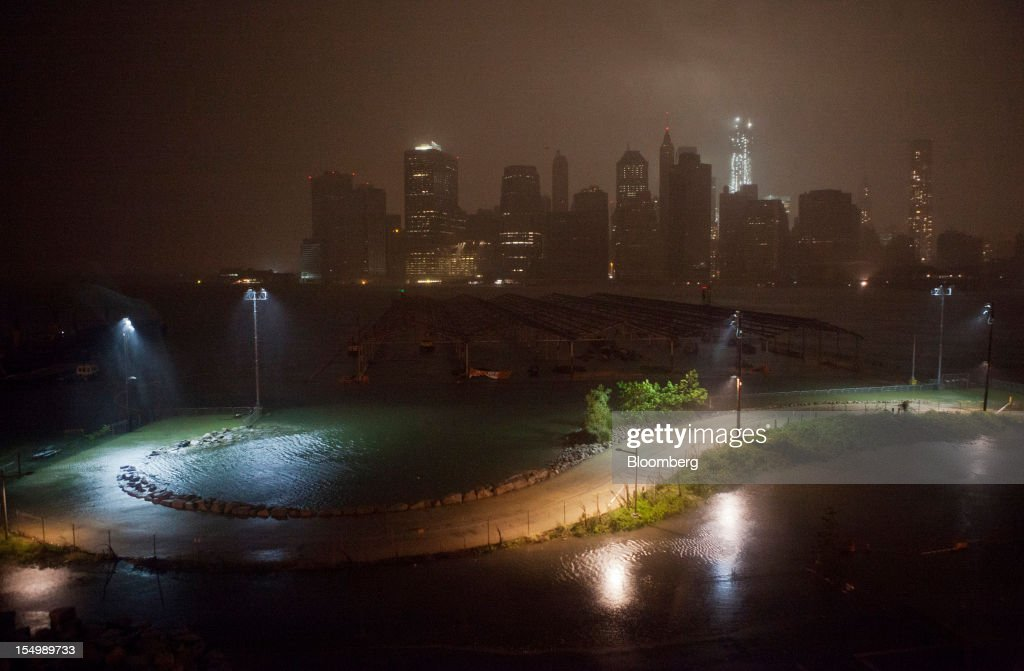 Flood waters cover a promenade in Brooklyn as numerous buildings in Lower Manhattan, background, stand in darkness in New York, U.S., on Monday, Oct. 29, 2012. Hurricane Sandy, the Atlantic's Ocean's biggest-ever tropical storm, barreled toward southern New Jersey after bringing a region with 60 million residents to a virtual standstill and upending the U.S. presidential race eight days before Election Day. Photograph: Victor J. Blue/Bloomberg via Getty Images