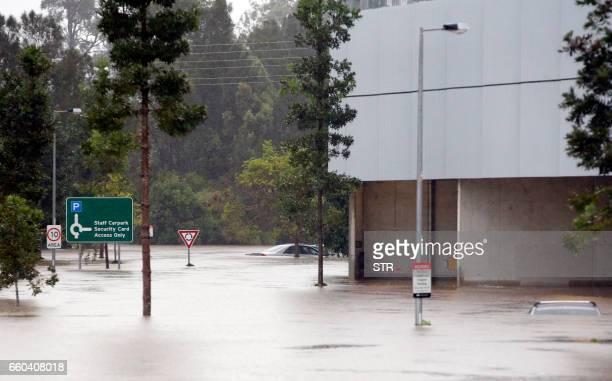 TOPSHOT Flood waters enter in the parking lot outside the Robina Hospital on the Gold Coast as severe rain continue throughout southeast Queensland...