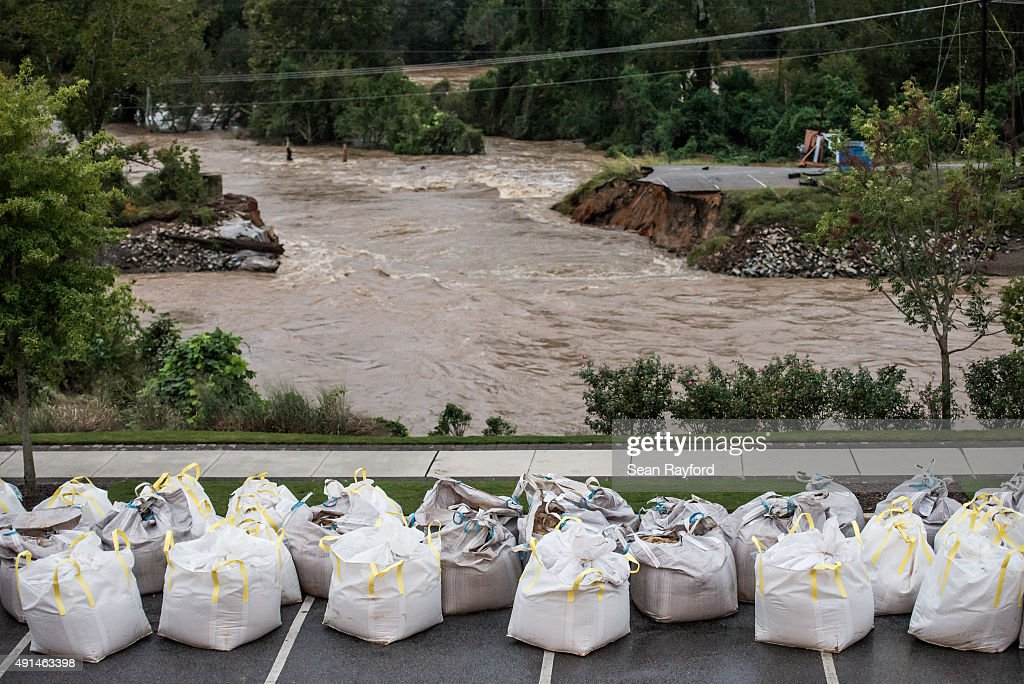 Flood waters rush through the breach of the Columbia Canal as emergency workers prepare giant sandbags to plug the hole October 5 2015 in Columbia...