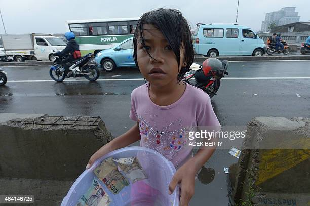 A floodaffected child begs on the street for money in Jakarta on January 21 2014 More than 4300 people in the capital have been displaced by the...