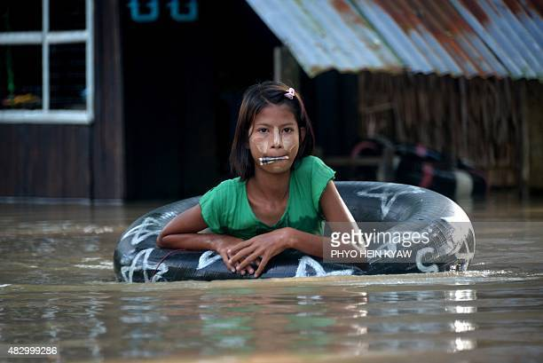 A floodaffected girl holds a mouthful of Myanmar currency called kyat as she uses a flotation tube at Nyaung Don township in Myanmar's Irrawaddy...