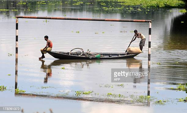 Floodaffected Indian villagers paddle their boat past a partially submerged set of football goalposts in the village of Mukata some 70 kms from...