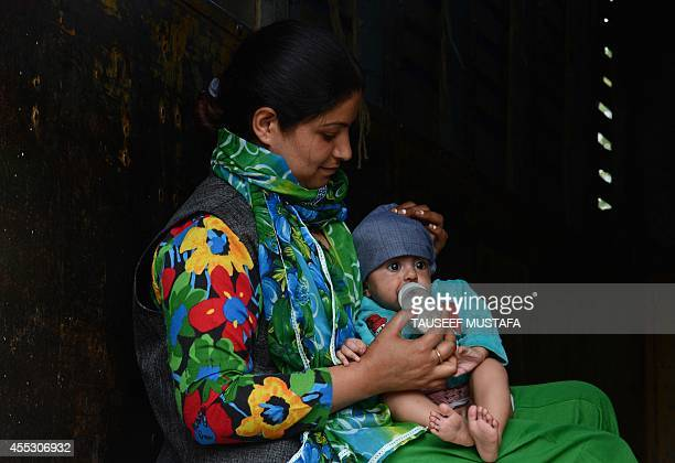 A floodaffected Kashmiri residents feeds a child inside a relief truck in central Srinagar on September 12 2014 The main city in Indian Kashmir has...
