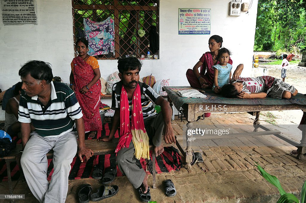 Flood-affected people sit at a local shelter in Allahabad on August 4, 2013. The monsoon, which covers the subcontinent from June to September and usually brings flooding, accounts for about 80 percent of India's annual rainfall. AFP PHOTO/ SANJAY KANOJIA