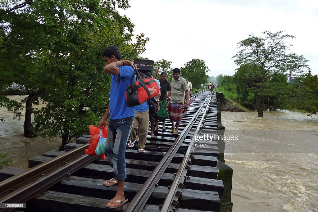 Flood-affected Sri Lankans walk on a railroad bridge across rising floodwaters in the eastern district of Polonnaruwa on December 23, 2012. Flash floods have killed at least 30 people in Sri Lanka and left more than a quarter of a million marooned in their homes, disaster officials said. Heavy rains, which have battered the island for much of the week, were still being reported in 14 of Sri Lanka's 25 administrative districts, with the central highlands -- one of the world's key tea producing regions -- the worst hit.
