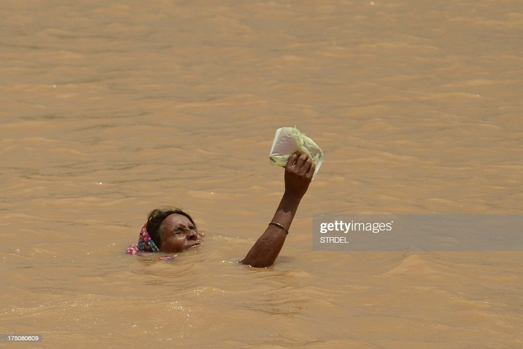 A flood-affected villager holds an item above water as she attempts to reach higher ground on the outskirts of Patna on July 31, 2013. The monsoon, which covers the subcontinent from June to September and usually brings flooding, accounts for about 80 percent of India's annual rainfall.