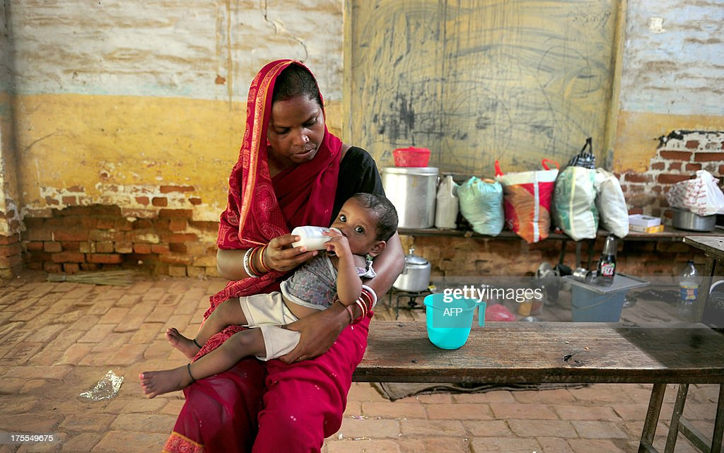 A flood-affected woman feeds her baby at a local shelter in Allahabad on August 4, 2013. The monsoon, which covers the subcontinent from June to September and usually brings flooding, accounts for about 80 percent of India's annual rainfall. AFP PHOTO/ SANJAY KANOJIA