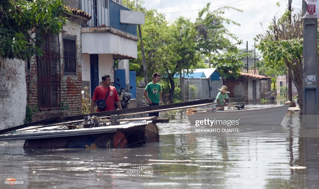 A flooded street in Asuncion on December 16 2015 The flood has forced more than 50000 people to leave their homes AFP PHOTO / Norberto Duarte / AFP /...